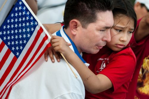 Child Facing Deportation with American Flag, Held by her Father