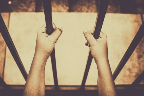 Child's hands holding iron bars
