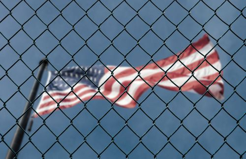 US American flag behind fence