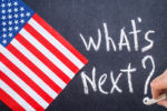 What's Next on a chalk board and US flag