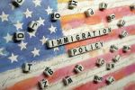 dice spelling immigration policy on an American flag