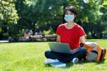 Student of Asian Heritage studies on laptop in park with medical mask