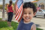 Little latino boy holding an American Flag